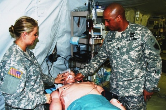 "Command Sgt. Maj.  Ron Joshua, command sergeant major of the 35th Combat Sustainment Support Battalion, ensures the tape around simulated casualty ""Phil"" is secure, while Spc. Amy Collins, a respiratory specialist assigned to the 325th Combat Support Hospital, assists."