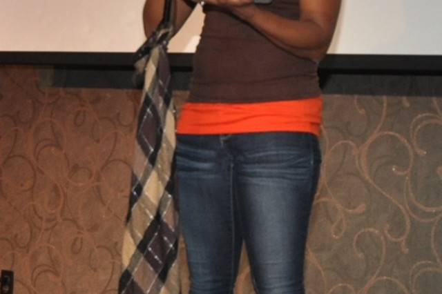 """Tiffany Rivera, BOSS volunteer, recites poetry that she wrote entitled """" Mirror Me,""""at Open Mic Night held at the R&R Bar and Grill, Aug.31. (U.S. Army photo by Sgt. Kevin Frazier)"""