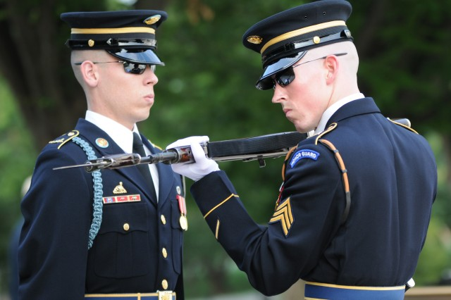 Sgt. Erik McGuire (right), Tomb Sentinel, Tomb of the Unknown Soldier, 3d U.S. Infantry Regiment (The Old Guard), inspects the weapon of a Tomb Guard during a guard change, Aug. 30, at the Tomb of the Unknown Soldier in Arlington National Cemetery, Va. Tomb Guards must pass a series of tests and training before they earn the right to be called a Tomb Sentinel.  (U.S. Army photo by Megan Garcia)