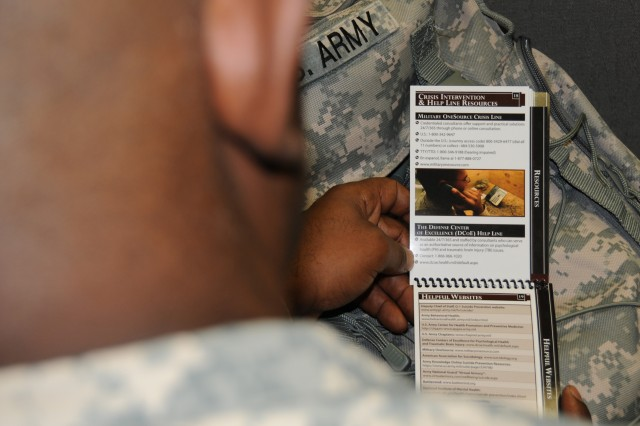 A senior NCO examines the Army Suicide Awareness Guide for Leaders, a comprehensive, quick reference for identifying Soldiers at risk and connecting them to suicide-intervention resources.