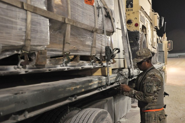 Spc. Walter G. Abad Yarleque, a truck driver with the 25th Transportation Company, straps down cargo on the back of an M-915 heavy truck on August 30, 2012 at Kandahar Airfield, Afghanistan. The 25th TC transports cargo to forward operating bases during night time tactical operations. (U.S. Army photo by Sgt. Gregory Williams)