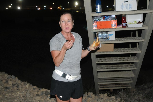 "During her 100-mile run, Sgt. 1st Class Rita ""Missy"" Rice carried her own water. There was no traffic stopped for her. No T-shirts or medals were handed out and there was no fanfare along the run. Rice, 12 hours into her run, gets a quick drink and a bite to eat."