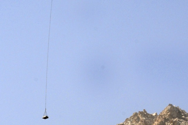 A CH-46 helicopter delivers supplies using long line position placement near the Salang tunnel, Afghanistan. The mission was the first conducted near the Salang tunnel to support Soldiers serving in support of Operation Enduring Freedom.