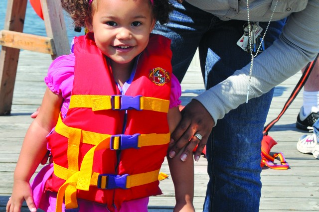 "Evan Heacock, wife of Spec. Jeremy Heacock, 2nd Brigade Special Troops Battalion, 2nd Brigade Combat Team, helps put a lifejacket on her 2-year-old daughter, Zoey, ahead of an antique boat ride on the St. Lawrence River aboard the ""Zipper."""