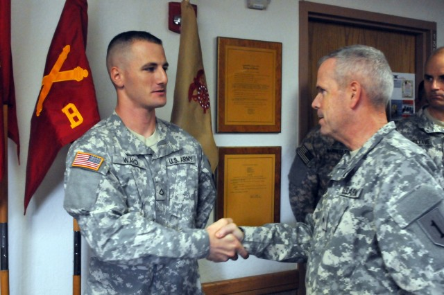 Pfc. Nicholas Ward, a fire direction specialist assigned to Headquarters and Headquarters Battery, 2nd Battalion, 18th Field Artillery, receives a commander's coin from Brig. Gen. Donald MacWillie, 1st Infantry Division deputy commanding general for support, Aug. 17 at Fort Sill. Ward was the winner of the Fort Sill and Fires Center of Excellence Soldier of the Quarter.