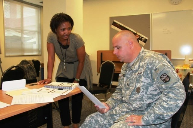 Staff Sgt. David Ladd, Patriot Missile Operator, 1/1 Air Defense Artillery, reviews course materials with Joanna Ashley, victim advocate, USAG Japan Torii Station, during the SHARP course on Okinawa.