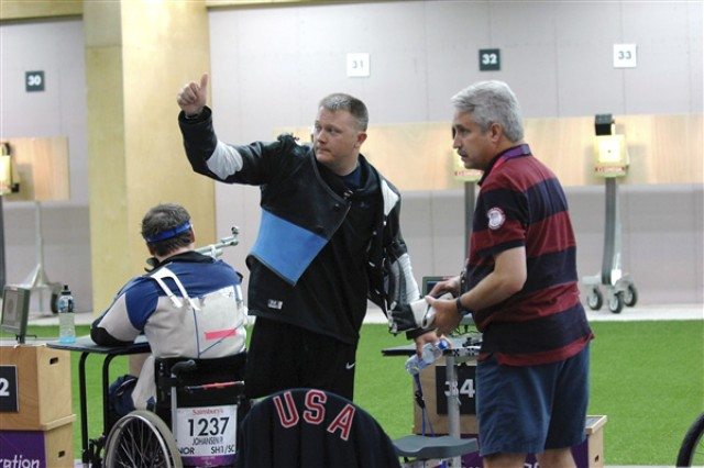 Sgt. 1st Class Joshua Olson, center, a member of the 2012 U.S. Paralympic shooting team, stands next to Bob Foth, his team coach, as he gives a thumbs up to his teammates after finishing a round of air rifle marksmanship during the Paralympic Games at the Royal Artillery Barracks in London, Sept. 1, 2012.