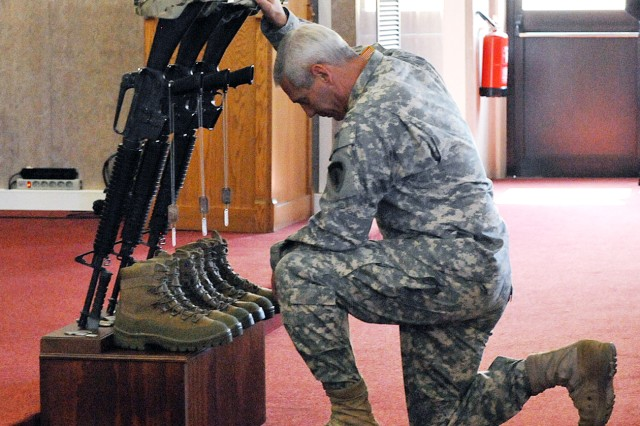 A fellow Soldier pays his respects at the conclusion of a memorial ceremony for three fallen Sky Soldiers at the Caserma Ederle post chapel Sept. 6.