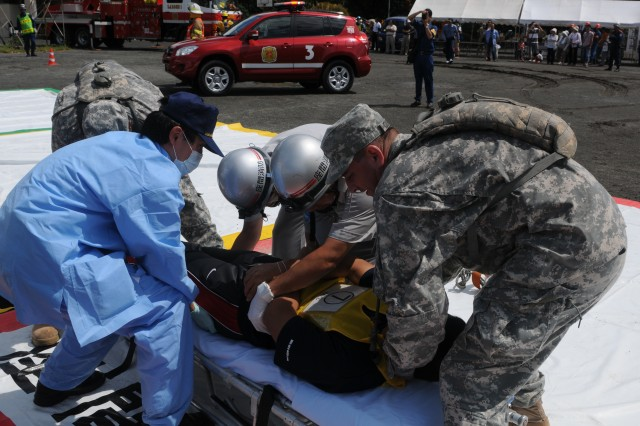 "Spc. Gene Siner, combat medic, Medical and Dental Command Japan, and Spc. Michael Corley, combat medic, Medical and Dental Command Japan helps city police, ambulance, fire department, search and rescue, and disaster assessment personnel in a Japanese disaster response drills exercise in Zama City Japan during U.S. Army Pacific's Medical Exercise 2012, 23 Aug. "" 2 Sept."