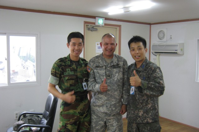 REPUBLIC OF KOREA-- 1st Lt. Lee and Capt. Choi, ROK Army and Air Force,. respectively, discuss engineer plans with Capt. Michael Huntanar. Lee and Choi are two of the liaisons assigned by the US Army Corps of Engineers Far East District to observe work by 368th FEST-Main at the Chilgok Stadium at Camp Carroll in Korea.