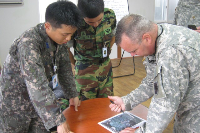 REPUBLIC OF KOREA--ROK service members, 1st Lt. Lee and Capt. Choi, observe as Maj. Camperson, U.S. Army Reserve 368th FEST-Main, briefs the survey of Chilgok Stadium during Ulchi Freedom Guardian 2012..