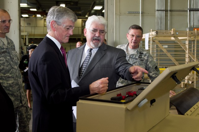 Joe Lackey, chief of Anniston Army Depot's Manufacturing Division, tells Secretary of the Army John McHugh how the installation manufactured backup battery containers for the SPARK II Mine Roller during McHugh's tour of the installation, Sept. 7, 2012. Also pictured in the photograph are Maj. Gen. Michael Terry, commanding general of TACOM Life Cycle Management Command and Col. Brent Bolander, the depot's commander.