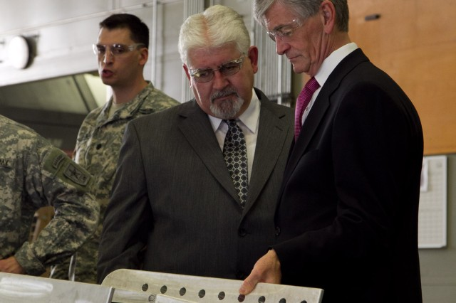 Joe Lackey, chief of Anniston Army Depot's Manufacturing Division, shows Secretary of the Army John McHugh examples of work performed by the installation's machinists during McHugh's tour of the installation, Sept. 7, 2012.