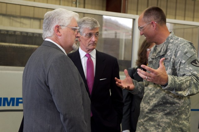 Secretary of the Army John McHugh discusses Anniston Army Depot's machining capabilities with Col. Brent Bolander, the depot's commander, and Joe Lackey, chief of Anniston Army Depot's Manufacturing Division, during McHugh's tour of the installation, Sept. 7, 2012.