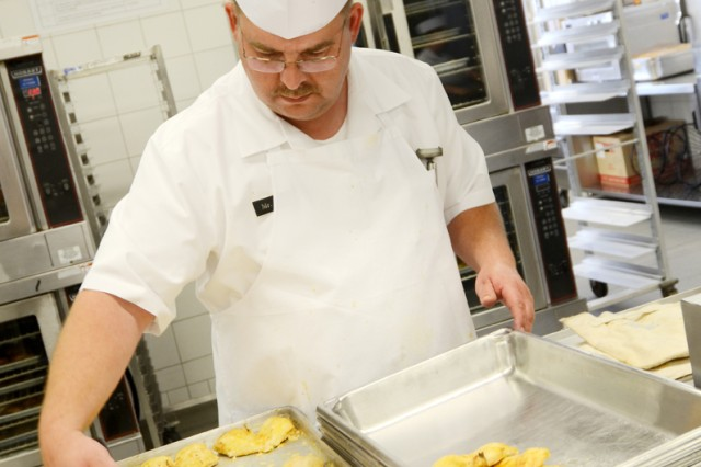 Stephan Ertl, a cook at the Lawrence T. Hickey Dining Facility, prepares fresh baked chicken for Soldiers of the NCO Academy in Camp Normandy.