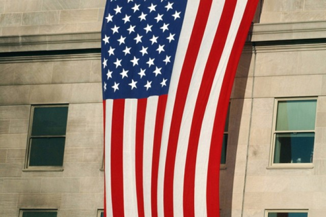"""As rescue and recovery efforts continued, fire fighters and rescue workers unfurled an American flag over the side of the Pentagon following the Sept. 11, 2001, terrorist attack. The flag, a garrison flag, was sent from by U.S. Army Band """"Pershing's Own,"""" based in Virginia."""