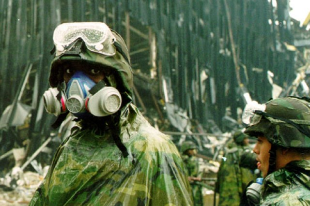 """Wearing a gas mask, a New York National Guard Soldier from the """"Fighting"""" 69th Infantry Division pauses amid the rubble at ground zero."""
