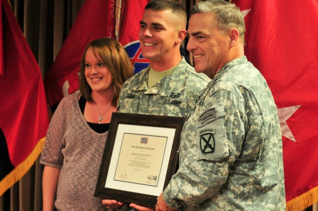 Maj. Gen. Mark A. Milley (right), Commanding General of Fort Drum and the 10th Mountain Division, presents Sgt. Richard Schuh, 4-25 Field Artillery Battalion, 3rd Brigade Combat Team, with a certificate from the USO acknowledging him as the USO Volunteer of the Year at a ceremony, Sept. 7. Schuh's wife, Beth, stands at the far left. (Photo by Sgt. Melissa Stewart)