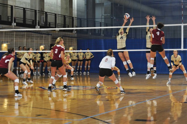 Colleen King of the Denver Pioneers (4) spikes a ball that is blocked by Alex Cassel (14) of the Navy women's volleyball team during Denver's win over the U.S. Naval Academy Midshipmen, in the first-ever service academy challenge hosted by the Pentagon, Sept. 7-8, 2012.
