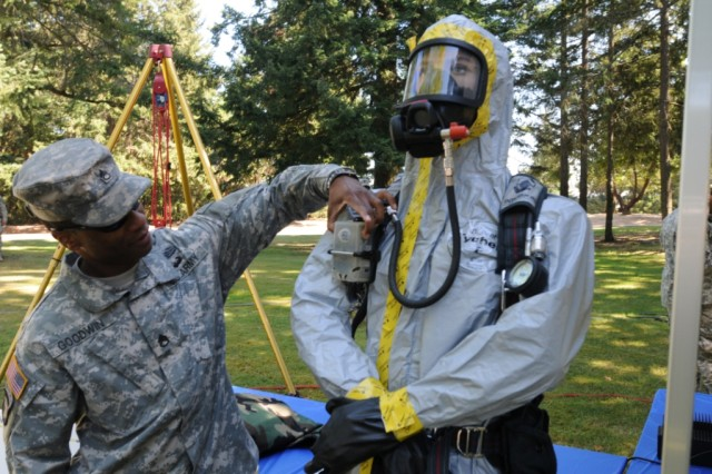"JOINT BASE LEWIS MCCHORD, Wash. - Staff Sergeant Devon Goodwin, 110th Chemical Battalion, tests the warning system of a hazardous materials protective suit used for Chemical, Biological, Nuclear, Radiological and Explosive missions during the 2012 Pacific Northwest CBRNE Conference. The theme for this year's conference was ""CBRNE professionals, partnering for the future."" Federal, state and local CBRNE response organizations were among those in attendance Sept. 5-7. (U.S. Army photo by Sgt. Mark Miranda)."