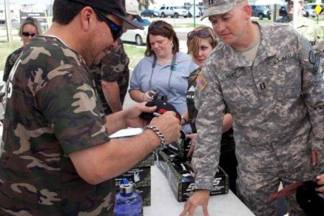 Cruz Pedregon driver and owner of Cruz Pedregon Racing, autographs a hot for Lt. Andrew Hunt, of Ft. Collins, Col., with Provincial Reconstruction Team Oruzgan, at the USO on Camp Atterbury Joint Maneuver Training Center, Ind., Aug. 24, 2012. The racing team was on Camp Atterbury as part of a crew swap program between members of Cruz Pedregon Racing and Soldiers at Camp Atterbury.