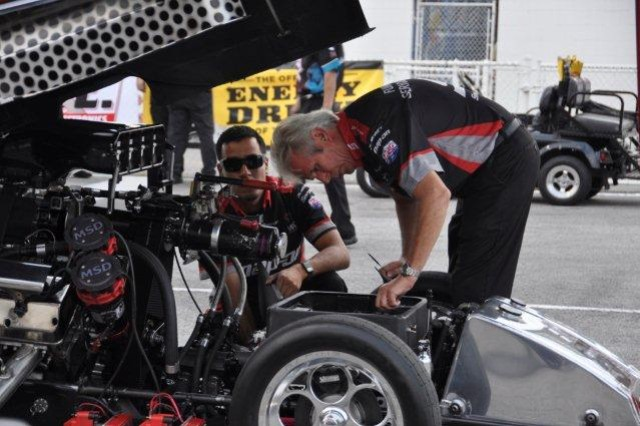 Two crewmembers from Cruz Pedregon Racing take a final look at their nitro Funny Car before a qualifying session at Lucas Oil Raceway Park in Indianapolis, Aug. 30, 2012. Members of Cruz Pedregon racing and civilians and Soldiers working at Camp Atterbury Joint Maneuver Training Center in Edinburgh, Ind., participated in a crew swap designed to show the importance of teamwork in military and civilian work environments.
