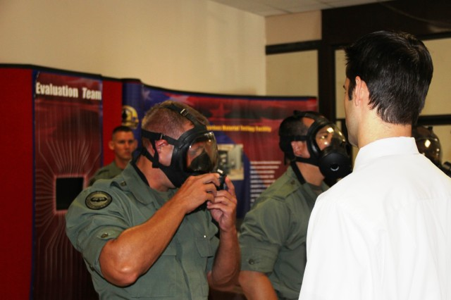 Steve Yurechko, right, helps a Maryland STATE officer adjust his gas mask before being tested in the corn oil chamber.