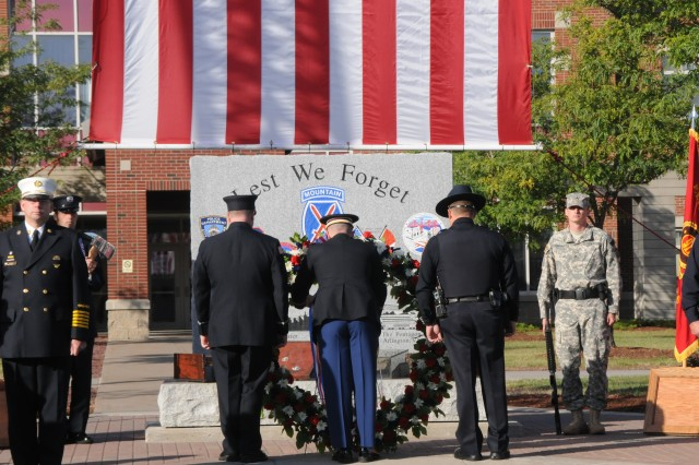Soldiers and Fort Drum emergency personnel place a wreath in front of the 9/11 Memorial in front of Clark Hall Tuesday during the annual 9/11 memorial ceremony.