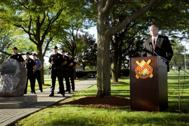 Alan Parks, garrison manager, U.S. Army Garrison - Detroit Arsenal, speaks to the crowd during the Patriot Day Ceremony as police and fire honor guard members stand at parade rest.