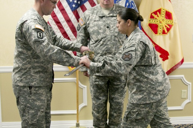 PICATINNY ARSENAL, N.J. - Master Sgt. Charless Gross (left) passes the noncommissioned officer sword to Command Sgt. Maj. Rosalba Dumont-Carrion (right) signifying assumption of responsibility and trust by the garrison commander. Lt. Col. Jason Mackay, garrison commander, looks on.