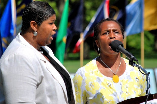 Jareen Johnson (left) and Everline Barnard, Army Sustainment Command, sing the national anthem during the Rock Island Arsenal Military Community 9-11 Remembrance Ceremony marking the 11th anniversary. (Photo by Jon Connor, ASC Public Affairs)