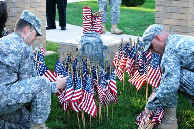 These Rock Island Arsenal Soldiers begin placing their flags following the Rock Island Arsenal Military Community 9-11 Memorial Walk. Each flag represents a life lost resulting from the attacks on the United States on Sept. 11, 2001, and those who died in subsequent action in defense of the nation in Operation Iraqi Freedom, Operation Enduring Freedom, and Operation New Dawn. (Photo by Susan Matos, ASC Public Affairs)