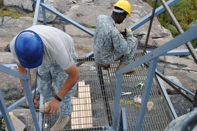 BEACON, NY -- Staff Sgt. Marco Padilla and Spc Osse Jean-Pierre, Soldiers assigned to the 1156th Engineer Company, New York Army National Guard, repair and replace railings on the Mount Beacon fire observation tower, September 7, 2012. The 1156th has stayed busy over the last year providing both military and community support ranging from aid to civilian authories during Tropical Storm Irene and Tropical Storm Lee to cleaning up the old Erie Canal.