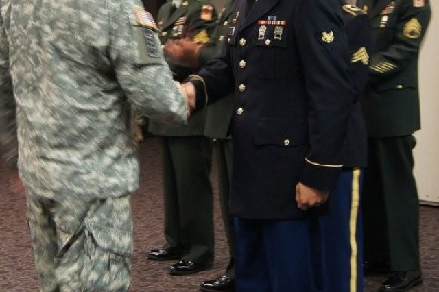 Lt. Col. John L. Donaldson, 11th Theater Tactical Brigade rear provisional commander, shakes Spc. David Wallen's hand after he was announced as the Noncommissioned Officer of the Year for the 11th TTSB, Sept. 5 at the brigade headquarters. Wallen is from Company C, 86th Expeditionary Signal Battalion.