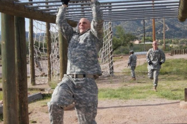 Capt. Brian Boundy, Headquarters and Headquarters Company, 11th Theater Tactical Signal Brigade, reaches for the last bars before moving onto the next obstacle while Sgt. Marcus Linquist runs up to complete the same obstacle. Their team finished the16 obstacles with the fastest time of 6 minutes, 40 seconds.