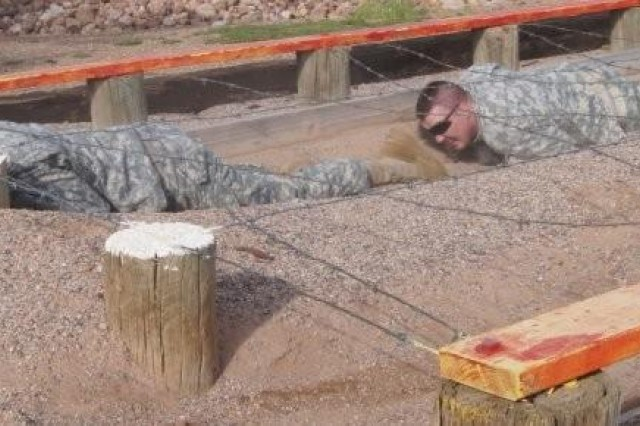 Cpl. Derek Nickey (left) and Spc. Chad Weaver ,Headquarters and Headquarters Company, 11th Theater Tactical Signal Brigade, low-crawl under barbed wire during training at the Apache Flats obstacle course. Low-crawling is a basic skill Soldiers learn during basic training as a method of staying low while moving effectively at the same time.