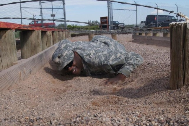 Spc. Sakenzalo Robinson low-crawls under barbed wire during training at the Apache Flats obstacle course.
