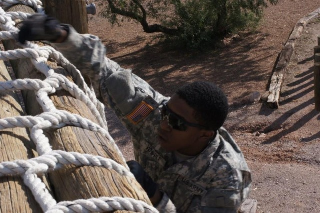 Spc. Antonio Whipple climbs the cargo net during the individual competition at the obstacle course at Apache Flats. After the Soldiers completed the course in teams, they were given the opportunity to compete against each other for the fastest time.