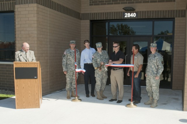 The ribbon is cut for the new Annual Training/Mobilization Barracks at Fort McCoy, Wis. Director of Public Works Darrell Neitzel is at the lectern. Also pictured, from left, are Garrison Commander Col. Steven W. Nott, TCI Architects/Engineers/Contractor Representative Matt Gobel, Cpl. Matthew Riley of the 86th Training Division, Omaha District Corps of Engineers Representative Nathan Butts, Four Bears Contractor Elmer Hanson and Garrison Command Sergeant Major Command Sgt. Maj. William T. Bissonette Jr.
