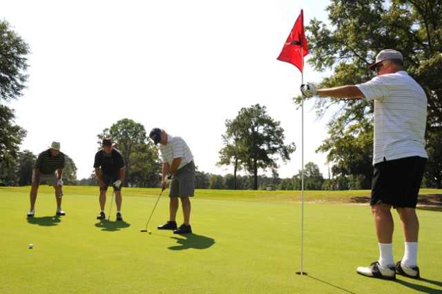 J.J. Goddard, Wayne White, Tim Luchner and Bob Raichle watch a shot during the Swing FORE Life Golf Tournament Sept. 7.