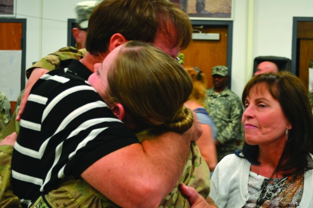 Wendell Meyers hugs his daughter, 1st Lt. Jenna Meyers, as her mother, Davetta Meyers, looks on. Meyers, who serves as a finance officer with 33rd Financial Management Company, 10th Sustainment Brigade Troop Battalion, returned from Afghanistan on Tuesday.