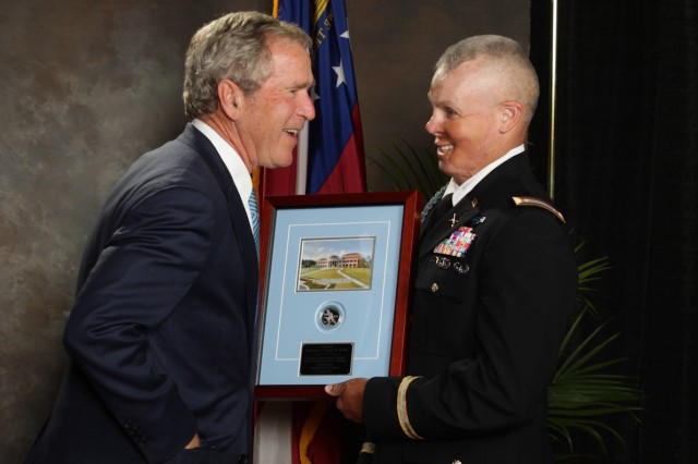 Lt. Col. Kevin Butler, a wounded warrior who commands the 2d Battalion, 19th Infantry at Fort Benning, Ga., presents a framed commemorative Infantry Soldier Silver Dollar to former President George W. Bush following his speech in Columbus, Ga.