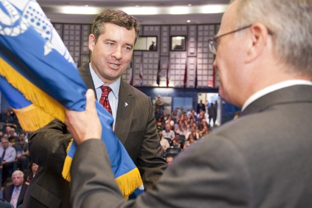 """Dale Ormond, left, director of the U.S. Army Research, Development and Engineering Command, passes the organizational colors to Dr. John P. """"Jack"""" Obusek during a Sept. 14 change-of-responsibility ceremony at Natick Soldier Systems Center."""