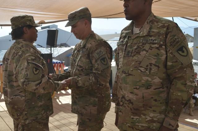 Sergeant Maj. Dannette D. Bailey, AFSBn-Bagram, 401st AFSB senior noncommissioned officer, accepts the noncommissioned officers sword from Lt. Col. Peter J. Koch, AFSBn-Bagram, 401st AFSB commander, during a change of responsibility ceremony at battalion headquarters Sept. 15  in