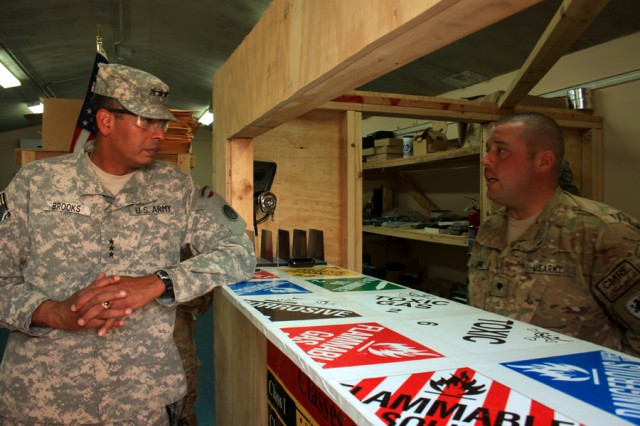 "Spc. Brian King (right) explains to Lt. Gen. Vincent Brooks, Third Army commander, how the Virtual Warehouse operates to re-circulate highly-demanded items to local units in the battlefield. This program effectively saves the U.S. taxpayer money in supplying Office supplies, computer cables, ""Chem-lights"" (disposable chemical light sticks) or similar surplus items to units in-need."
