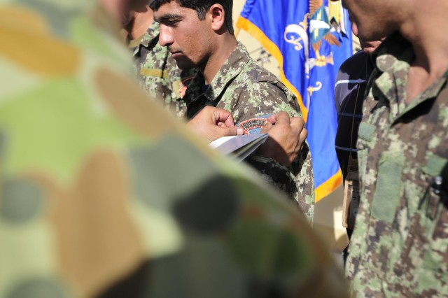 An Afghan soldier with the Pathfinder Platoon, 4th Kandak, 2nd Brigade, 205th Corps, receives his ranger tab during the graduation ceremony from the Afghanistan Pathfinder Partnership Academy hosted by Pathfinders from Company F, 2nd Battalion, 25th Aviation Regiment, 25th Combat Aviation Brigade, at Forward Operating Base Wolverine, Afghanistan, Sept. 12.