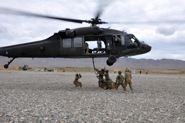 Soldiers of the Pathfinder Platoon, 4th Kandak, 2nd Brigade, 205th Corps supervised by Pathfinders from Company F, 2nd Battalion, 25th Aviation Regiment, 25th Combat Aviation Brigade, sling-load a package to the bottom of a UH-60 Black Hawk during the Afghanistan Pathfinder Partnership Academy at Forward Operating Base Wolverine, Afghanistan, Sept. 11. (Photo by: 1st Lt. Cassie Graham by 25th Combat Aviation Brigade Public Affairs)