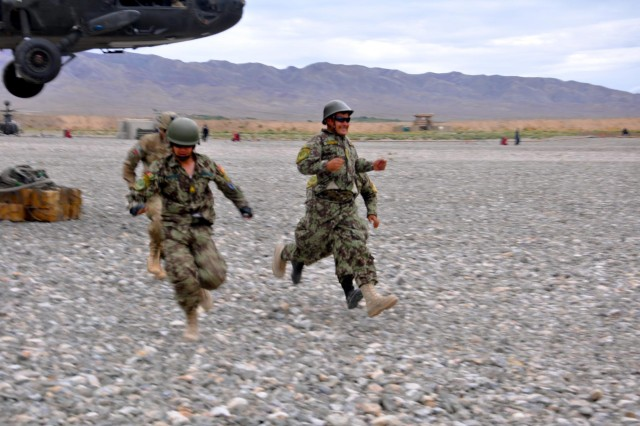 Soldiers of the Pathfinder Platoon, 4th Kandak, 2nd Brigade, 205th Corps supervised by Pathfinders from Company F, 2nd Battalion, 25th Aviation Regiment, 25th Combat Aviation Brigade, move swiftly away from a UH-60 Black Hawk after sling-loading a package during the Afghanistan Pathfinder Partnership Academy at Forward Operating Base Wolverine, Afghanistan, September 11. (Photo by: 1st Lt. Cassie Graham by 25th Combat Aviation Brigade Public Affairs)