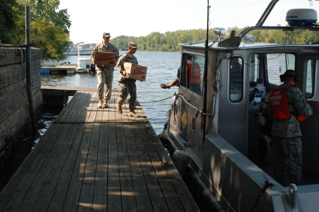 Soldiers of the New York Army National Guard's 42nd Infantry Division deliver supplies to New YORK Naval Militia Patrol Boat 230 during a domestic operations exercise conducted Sept. 14, 2012, at Troy, N.Y. The mission called for the Naval Militia boat to deliver supplies provided and moved by Army National Guard logisticians to citizens stranded on an island during a hurricane. A New York Air National Guard Airman from the 109th Airlift Wing provided communications support for the mission.