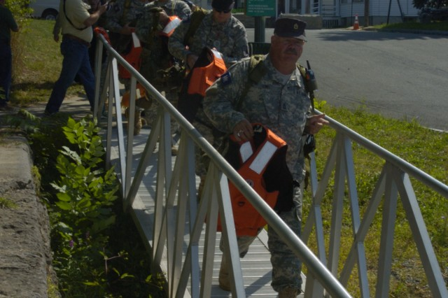 Members of a New York Guard (state defense force) Search and Rescue Team prepare to board a New York Naval Militia patrol boat during a hurricane relief exercise, Sept. 14, 2012,at Troy, N.Y.  Members of the National Guard, Air National Guard, New York Guard and New York Naval Militia, who normally train separately, all came together during the exercise.